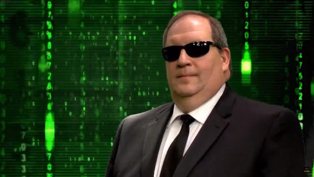 A person wearing a suit and sunglasses posing for the camera  Description automatically generated